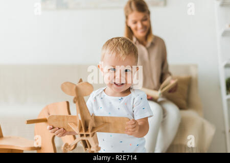 happy toddler playing with toy wooden toy plane in nursery room with mother on background