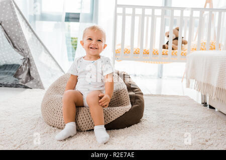 adorable smiling toddler sitting on bean bag chair  in nursery room - Stock Photo