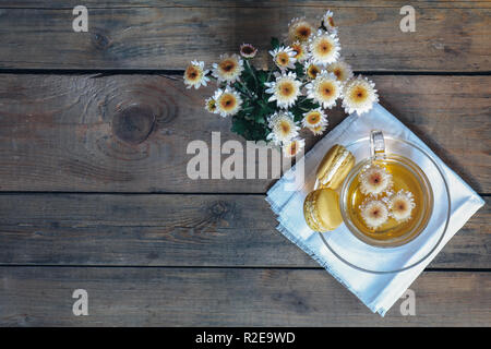 Cup of tea with chrysanthemum flowers and macaroons on the dark wooden surface, top view, copy space, cinematic color. - Stock Photo