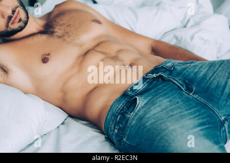 cropped image of shirtless man with muscular torso laying in bedroom at home - Stock Photo