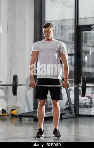 handsome athletic bodybuilder training with barbell in gym - Stock Photo