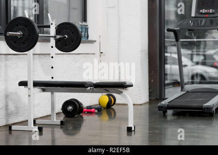 treadmill, barbell and weights in modern gym - Stock Photo