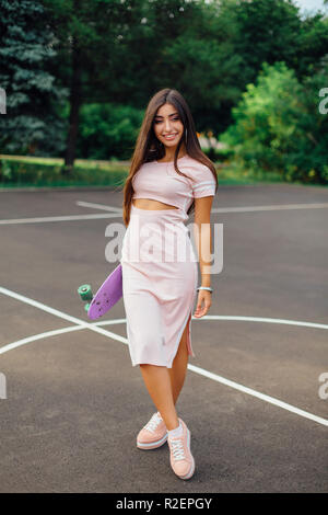 Portrait of a smiling charming brunette female holding in hand her skateboard on a basketball court. Happy woman with trendy look taking break during  - Stock Photo