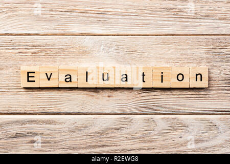evaluation word written on wood block. evaluation text on table, concept. - Stock Photo