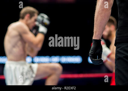 referee in black clothes in ring two fighters MMA, boxing martial arts competition - Stock Photo