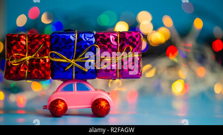 Pink toy car delivers Christmas presents on the background of the night city. Web banner. For the blog. - Stock Photo