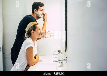 happy couple at home enjoy lifestyle in the bathroom. young beautiful man doing and cutting the beard with sponge and the cheerful lady stay with him laughing and joking together. playful activity for nice couple - Stock Photo