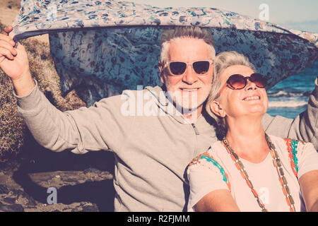 happy couple of senior people gentleman and lady sit down near the ocean with hippy colored clothes style. enjoy and have fun with alternative lifestyle. cheerful caucasian people enjoying the vacation together - Stock Photo