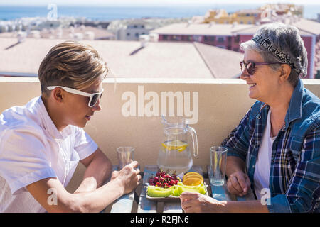 happy leisure activity on the terrace rooftop having breakfast with smiles and happiness for grandmother and teenager family caucasian people. ocean and buildings view, outdoor coule together - Stock Photo
