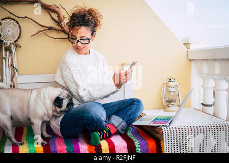 Happy alternative young cheerful woman warking at home with a new business way. sitting on a bench outdoor at home with best friend old pug together. colorful bench and lifestyle. laptop and phone to communicate and internet - Stock Photo