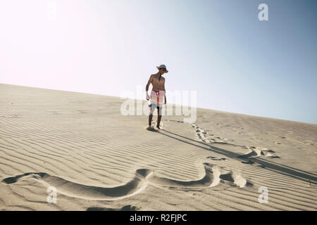 lost in happiness in the middle of the desert with sand dunes. young happy boy teenager enjoying vacation at the beach. clear blue sky in background. swimsuits and signs on the sand. summer day - Stock Photo