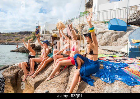 group of nice and beautiful females friends smiling together having fun in friendship summer leisure time outdoor near the beach. swimsuits and ladies enjoyed the weather and the sun. vacation and fun for group of caucasian people - Stock Photo