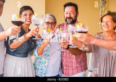 happy group of different ages people celebrating and having fun together in friendship at home or restaurant. cheering and toasting with cocktails and alchool. smile and enjoy the party with adult and middle age people. - Stock Photo