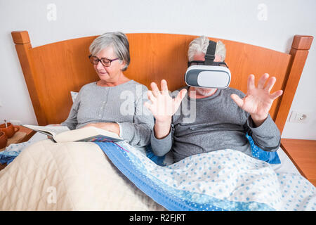 nice beautiful couple caucasian matures man and woman at home in the bedroom stay on the bed during a morning. she read a paper book and he play and use goggles headset trying new technology experience - Stock Photo