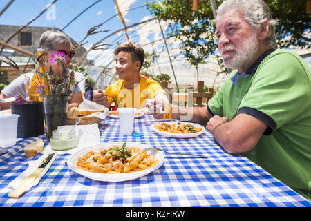 grandfathers and grandson together in an alternative biological nature concept restaurant with italian food pasta on the table having fun in friendship smiling and speaking. family at lunch in holiday concept - Stock Photo
