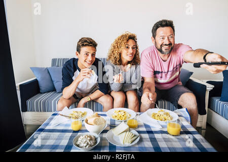 Happy caucasian family mother father son beautiful cheerful happy people having lunch at home together smiling and enjoying. home interior lifestyle concept for group of people with different ages looking tv - Stock Photo