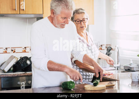 senior adult caucasian couple at home preparing dinner or lunch together. relationship and family lifestyle for people married in love. real people scene in the kitchen. together relationship forever concept - Stock Photo