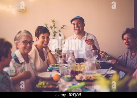 happy group of different ages people celebrating and having fun together in friendship at home or restaurant. cheering and toasting with cocktails and alchool. smile and enjoy the party with adult and middle age people. event with food and wine - Stock Photo