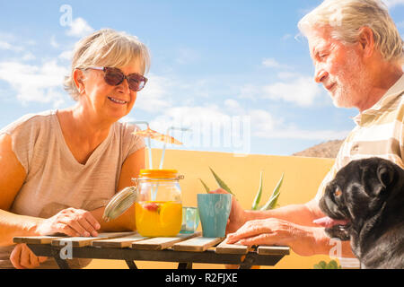 couple of aged gentlemen and lady drinkk together fruit juice on rooftop terrace wih two funny pug dog under the sunlight. amazing ocean view for great retired lifestyle concept - Stock Photo