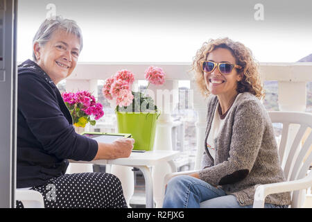 couple of women friends stay in the terrace together enjoying the friendship at home. using technlogy internet connected tablet and smile to the camera. beautiful middle age and senior females friends - Stock Photo