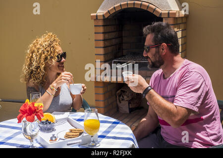 nice cheerful caucasian couple having breakfast outdoor at home near a grill barbecue. smile and spent sime good time together for adult couple. - Stock Photo