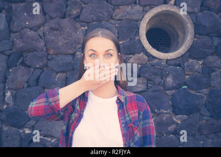 shut up and silence no words surprise and surprised concept with a beautiful woman portrait with stone dark wall in background. big open eyes and hand in front of the mouth to close it - Stock Photo