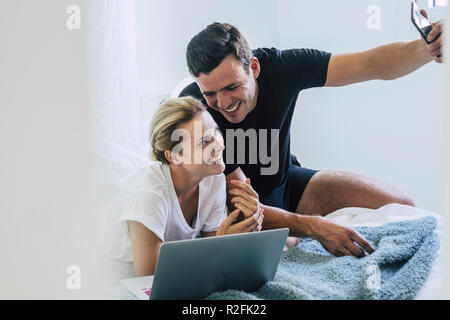 joy and happy beautiful caucasian couple at home in the bedroom on the bed using computer and taking a selfie picture with the smartphone. laugh and happiness for boy and girl in our life. cheerful people indoor - Stock Photo