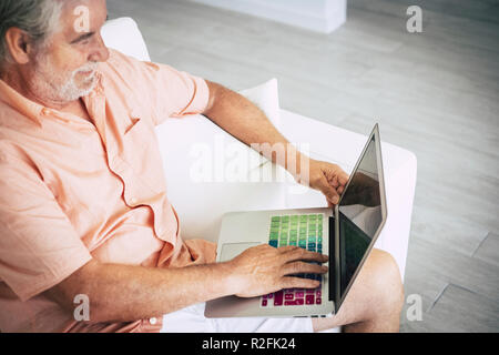 senior adult white hair aged caucasian man viewed from above using a colored laptop to search on the web. online commerce shopping and search engine for health and hobby time. home interior lifestyle - Stock Photo