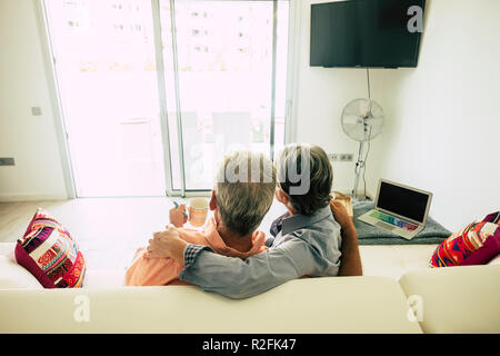 couple of senior sitting at home on a white sofa looking outside te window door to the garden. enjoying retired time relaxing together with love and satisfaction for the end of the work. laptop on the side - Stock Photo