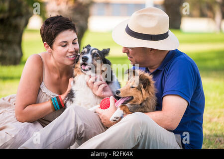 middle age caucasian couple in outdoor leisure activity with best friends dogs all together having fun and love like an alternative family. happiness and enjoy lifestyle for cheerful people and animals - Stock Photo