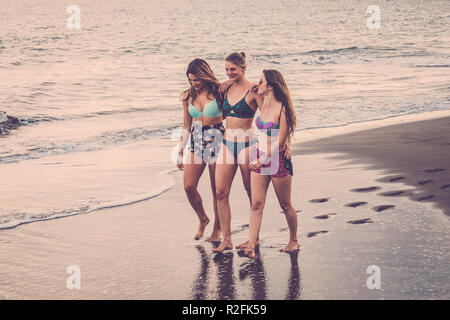 three caucasian cheerful young women walk together hugged on the shore at the beach. summer lifestyle outdoor activity for beautiful girls in vacation. smiling days and happiness. Vintage filter and color - Stock Photo