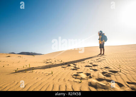 single man explorer in the desert with jacquet equiment and backpack traveling and walking barefoot. discover the beauty of the world in alternative vacation and lifestyle. wanderlust concept for caucasian people - Stock Photo