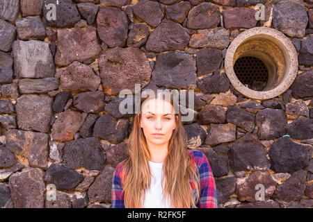 beautiful portrait of enigmatic young beautiful 30 years old woman standing under a stone wall and looking at the camera no smiling. hole in the background. long blonde hair and beauty concept - Stock Photo