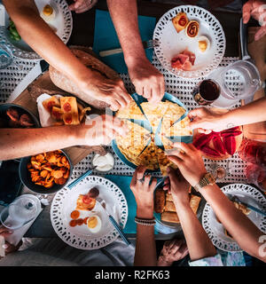 Aerial view from above for table and hands and a lot of food and drinks. celebration and party event concept image. all hands taking from the same plate to share and enjoy the friendship. caucasian people easting together at the restaurant - Stock Photo