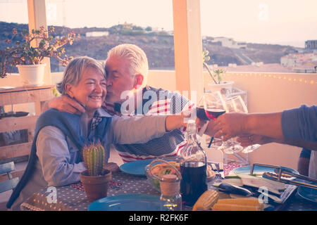 group of aged senior friends adults having dinner and doing party nice time in the rooftop terrace outdoor with wine and food. having fun and kiss  during the sunset with beautiful sun backlight and amazing view of the ocean and other roofs. - Stock Photo