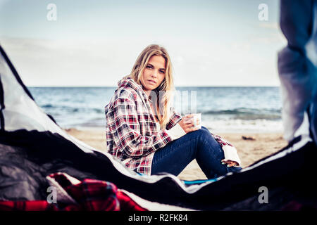 wild vacation alternative on the beach with a tent for a beautiful blonde female taking a mug with hot drink. Look at camera and rest. Alternative life concept. - Stock Photo