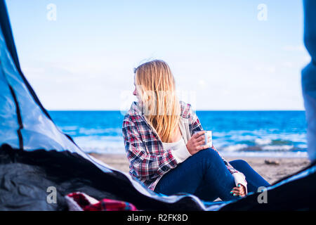 alternative life and vacation concept for blonde cute girl sit down looking at the ocean on the door of her tent. Tenerife locetion. - Stock Photo