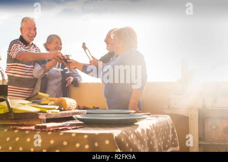 group of senior people doing party and barbeque outdoor at the terrace rooftop. celebration and event time at the sunset. happiness and nice lifestyle - Stock Photo
