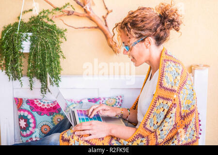 full of color image for middle age woman working freedom at laptop outdoor in the terrace, plants and nature in the background for independence concept - Stock Photo