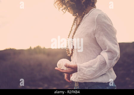 nice cut for beautiful middle age 40 years old model lady immersed in the nature of a desert. she take a shell on her hand for nature connection concept. tenerife magic place for vacation - Stock Photo