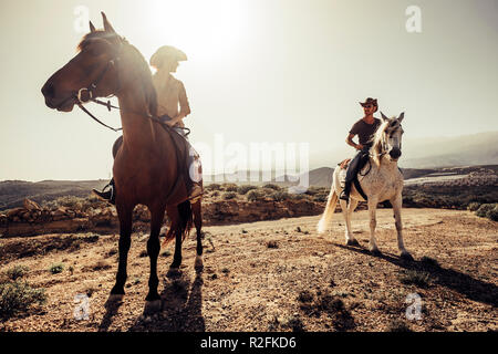 couple of horses and cowboys male and female ride free in the nature at the mountains in tenerife. lifestyle and alternative works or leisure activity concept for man and woman - Stock Photo
