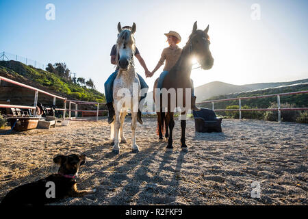 beautiful caucasian couple on two horses with the sun in backlight and a dog looking them from the ground. touching hands and beautiful animals for love therapy Stock Photo