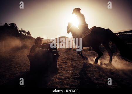 hero concept dramatic and advertising style image for cowgirl making dust riding a horse near a cowboy sit down on a chair in the middle of the track. another horse in background. alternative leisure activity - Stock Photo