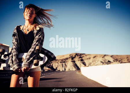 freedom and alternative lifestyle outdoor concept for beautiful blonde young woman walking on the street with skateboard and wind in the hair. enjoying life and day time. warm colors. - Stock Photo