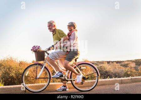 two senior man and woman together on  an old bicycle outdoor activity. happyness and freedom from work concept. sunlight and smiles. - Stock Photo
