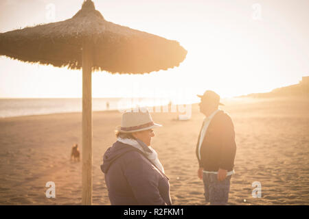Couple of separated man and woman elderly looking to different separated directions with backlight from the sunset. Thought concept in spring near the ocean. - Stock Photo