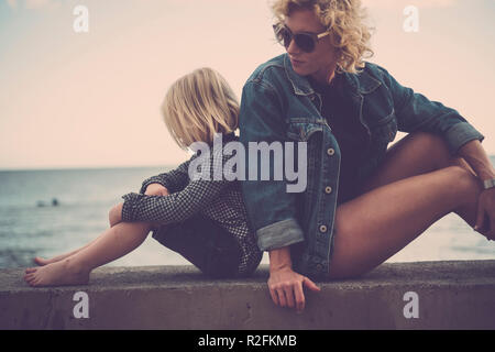 mother and son woman and male blonde both stay sitting together by back and enjoying the sea and the nature around them. vacation and emotion feeling for family and people - Stock Photo
