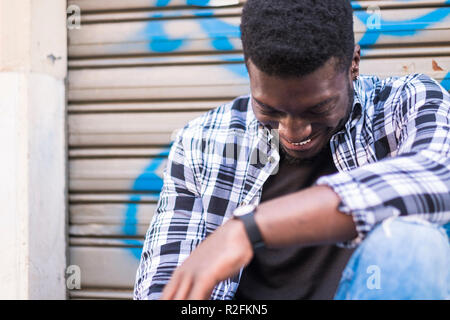 Handsome cheerful beautiful young black man african american smiling and having fun while sit and relax in the city with urban background. youthful concept for hipster style teenager boy - Stock Photo