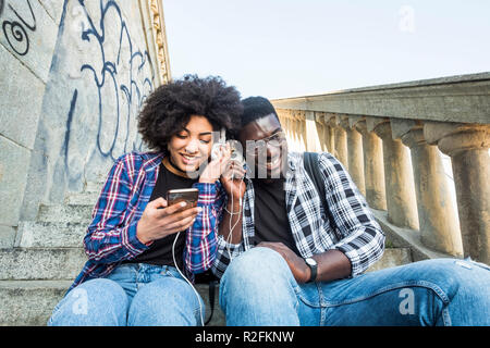cheerful happy black africann couple sitting togethe in friendship listening music from a modern phone and sharing the headphones like partners. smiling and having fun - Stock Photo