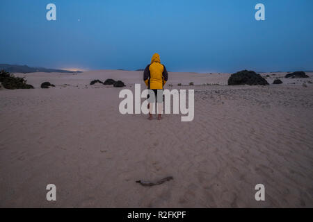 single man with yello jacket wait and stand in the middle of the desert of corralejo fuerteventura by night in the evening. cold and enjoying the nature around wth nobody for alternative vacation and lifestyle concept - Stock Photo